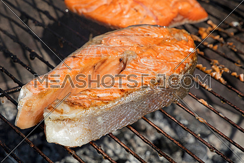 Grilled salmon fish steak barbecue meal cooking, prepared on bbq grill, close up