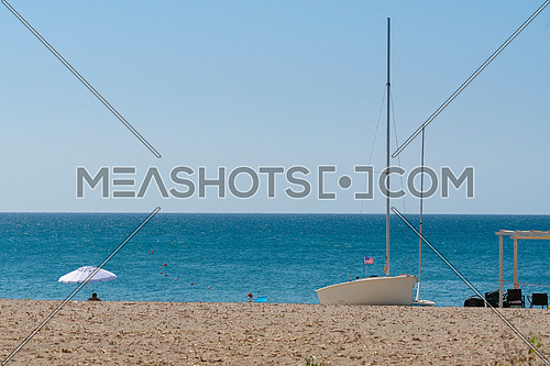 anchored boat with american flag on sandy beach and blue sea,one isolated umbrella beach, sunny day ,Summer vacation concept.