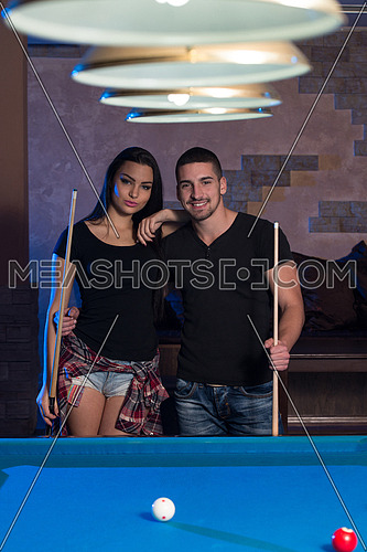 Portrait Of A Young Couple Playing Billiards