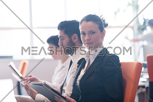 business woman on meeting usineg tablet computer, blured group of people in background at  modern bright startup office interior