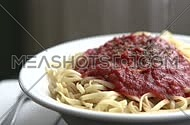 hand putting spaghetti plate on table
