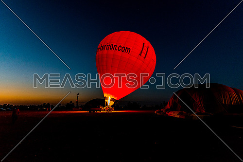 A red Hot Air Balloon preparing to takeoff in Luxor by dawn