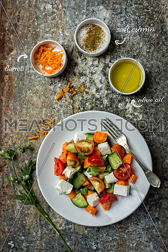 Top view of green salad dish with oil, carrots, salt and cumin  on marble table top