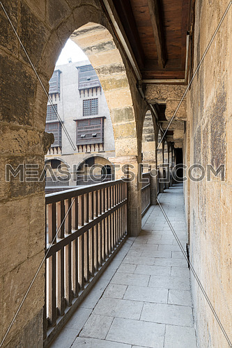 Angled view of one arch with interleaved wooden balustrades at the arcade surrounding the courtyard of caravansary (Wikala) of Bazaraa, Medieval Cairo