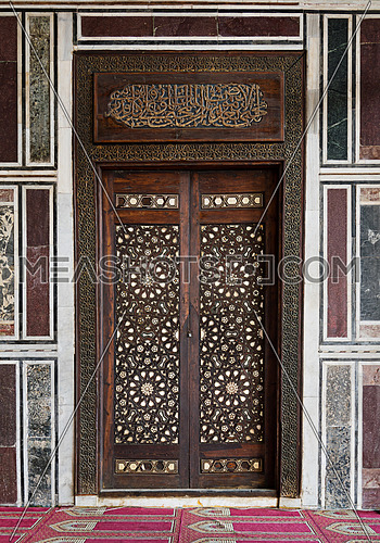 Old decorated wall with a historic ornate wooden door in an old mosque, Cairo, Egypt