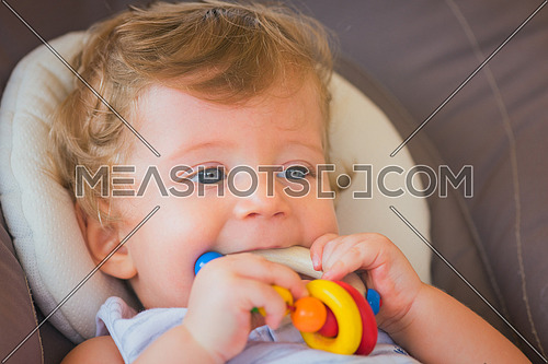 caucasian white baby boy playing with toy