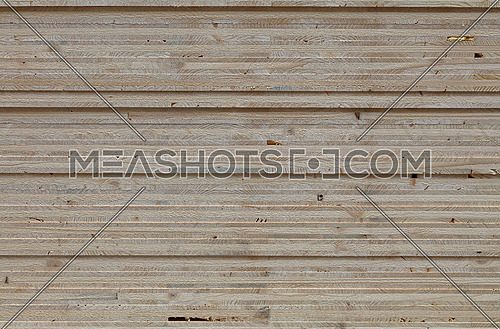 Background texture of wooden OSB board butt ends stacked, close up, low angle view