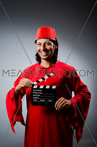 Man wearing fez hat with movie board