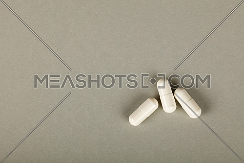 Close up three white gel cap pills of medicine over grey background with copy space, elevated high angle view, directly above
