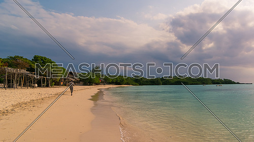 In the picture a man walking alone on a beautiful beach in Zanzibar in the evening. Republic of Tanzania.