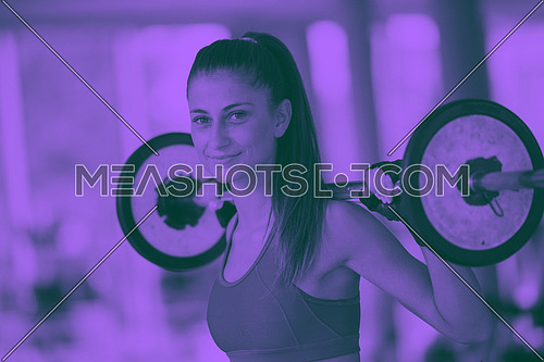 healthy and fit young woman in fitness gym lifting weights and working on her butt muscles duo tone