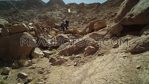 Reveal shot for group of tourists climbing big rocks with bedouin guide to explore Sinai Mountain for wadi Freij at day.