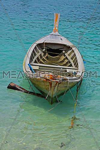 Traditional Thailand old vintage unpainted long tail boat without engine in transparent turquoise water