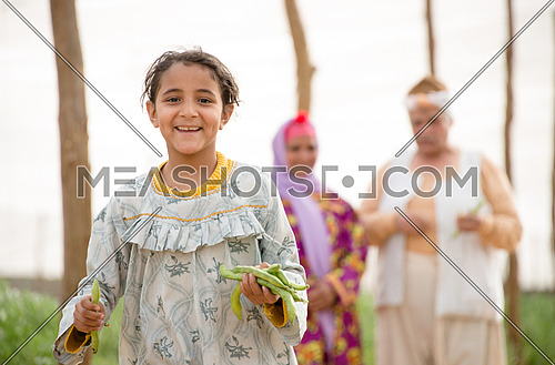 A happy farmer girl running holding raw broad beans in her hands