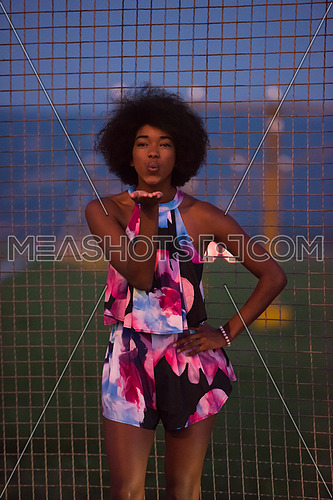 portrait of a young beautiful African American women on a warm summer night  in summer dress with a smile on her face