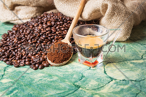 Coffee beans in coffee burlap bag on green table,wooden spoon with ground coffee on top and coffee glass cup.