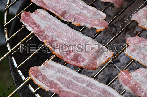 Raw smoked melting grilled barbecue bacon slices, being cooked on round bbq smoke grill, close up