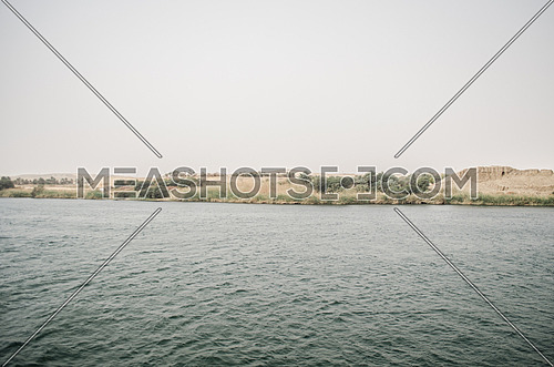 A landscape of the Nile river water and sand mountains and plants by the shore