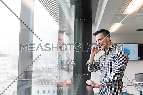 relaxed young businessman speaking on smart phone at modern startup business office meeting room  with big window and city in backgronud