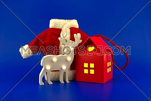 Stylized wooden reindeer house shaped gift box with yellow glowing windows and red Santa Claus suit on a festive blue background. New Year and Christmas holiday season concept card decoration