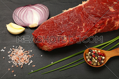 One raw beefsteak red meat cut, spices, peppercorn in wooden scoop, green spring chive, onion, garlic and Himalayan salt on black slate board, close up, high ange view