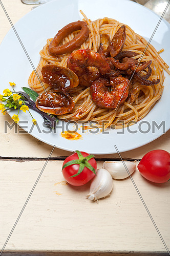 Italian seafood spaghetti pasta on red tomato sauce over white rustic wood table