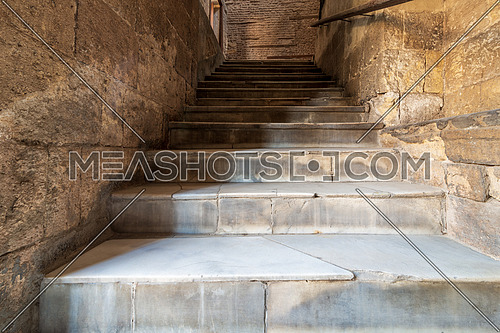 Day shot of old narrow stone staircase ending with bricks wall