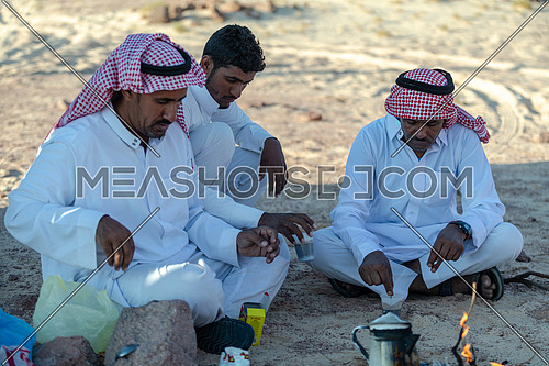 Bedouin Males wearing traditional clothing, sitting and making tea at Ain Hodouda area in Sinai at day.