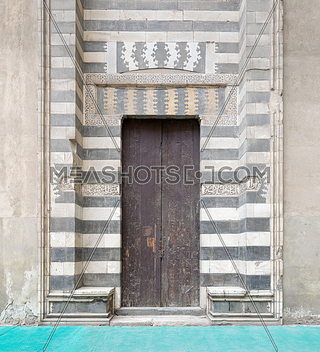 Wooden aged door surrounded by striped black and white marble decorations and stone wall at the Mosque of Sultan Hasan, Medieval Cairo, Egypt