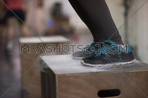 box jumping at a crossfit style gym. Female athlete is performing box jumps at gym with focus on legs
