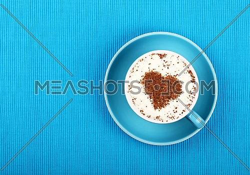Close up one latte cappuccino coffee with heart shaped chocolate milk topping in red cup with saucer over background of blue tablecloth, elevated top view, directly above