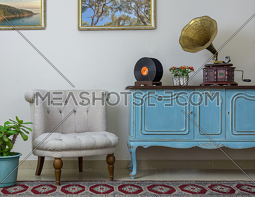 Vintage interior of retro off white armchair, vintage wooden light blue sideboard, old phonograph (gramophone) and vinyl records on background of beige wall, tiled porcelain floor, and red carpet