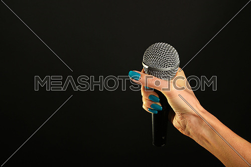 Woman hand with blue nails holding microphone isolated on black background