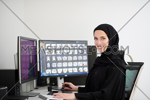 Muslim female graphic designer working on computer using graphic tablet and two monitors. Girl wearing hijab editing photos in the office