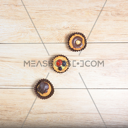 Pictured pastries on light wood background,above view,square photo.