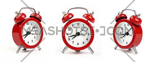 Three small red metal alarm clock with red bells over white background, close up, low angle view in different perspectives