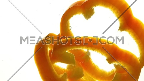 Close up several cut slices of fresh yellow orange bell pepper thrown and floating in clear transparent water, low angle side view, slow motion
