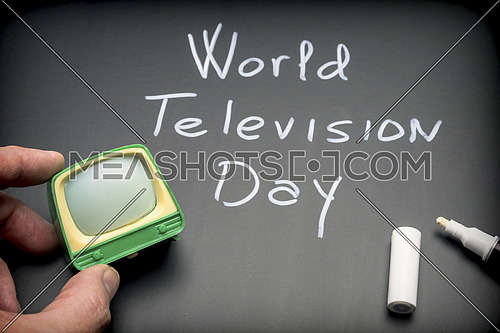 World Television Day written on Blackboard next to miniature TV, conceptual image