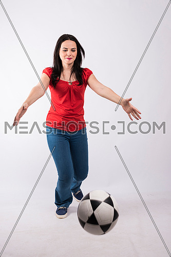 young lady standing and playing with a ball on white background wearing red shirt and jeans