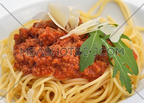 Italian spaghetti topped with bolognaise, or bolognese, sauce with tomatoes, meat and cheese on a plain white plate