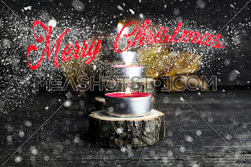 Merry Christmas. Christmas candles burning, decoration on wooden logs resting on rustic wooden background with Snow Flakes And Stardust