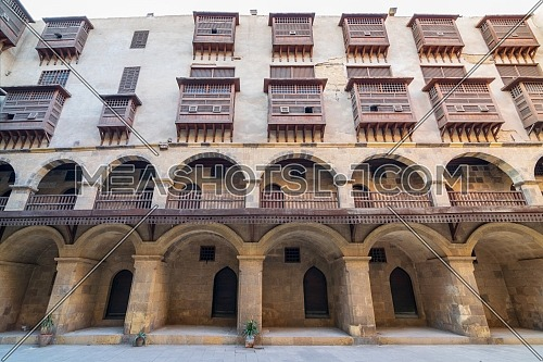 Facade of historic Wikala of Bazaraa building, with vaulted arcades and oriental wooden oriel windows, suited in Tombakshia street, Gamalia district, Medieval Cairo, Egypt