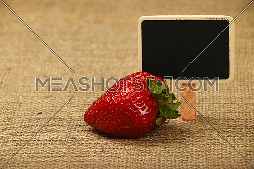 One mellow fresh red summer strawberry with chalk blackboard price tag sign on jute burlap canvas background