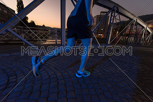 urban sports, young healthy man jogging across the bridge in the city at early morning in night