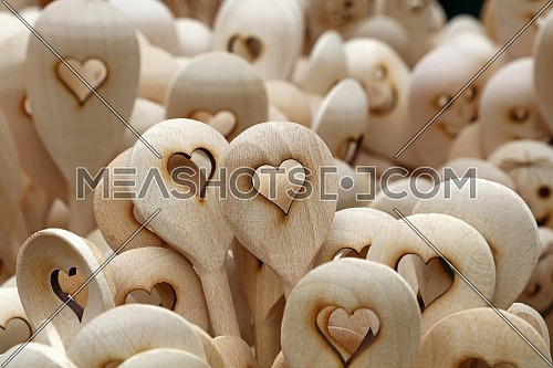 Close up handmade rustic wooden cooking spoons with carved heart shape at retail market stall display