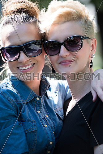 Young beautiful women with sunglasses posing in a park on a sunny summer day