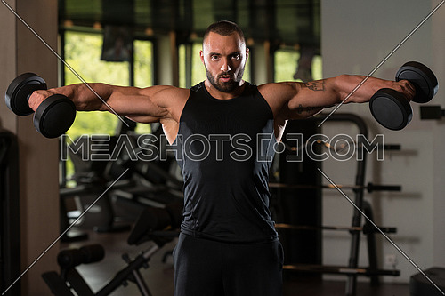 Big Man Standing Strong In The Gym And Exercising Shoulders With Dumbbells - Muscular Athletic Bodybuilder Model Exercise In Fitness Center