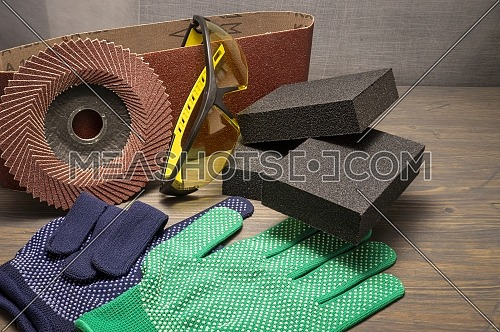 Different tools for sanding - sanding belt, clamps, abrasive sponge and flap disc for angle grinder, safety gloves and goggles, renovation, safety and health at work concept