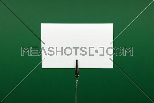 Blank white cardboard sign with copy space on metal note holder over green paper background, front side view