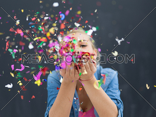 beautiful young woman celebrating new year and chrismas party while blowing confetti decorations to camera isolated over gray background